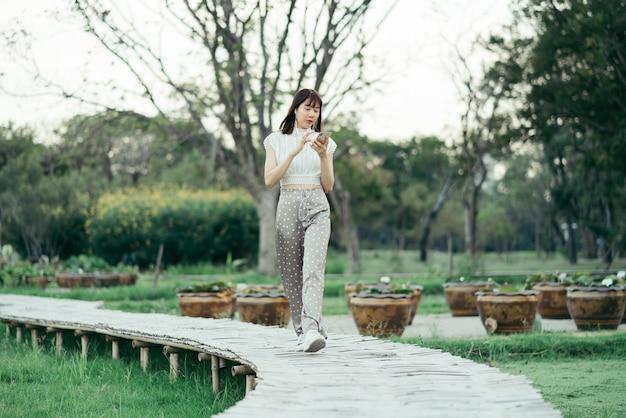 Gelukkige jonge vrouw in witte kleren met oortelefoons gebruikend mobiele telefoon luisterend aan muziek met haar ogen bekijkend het scherm genietend van haar ogenblik terwijl het wandelen op houten gang in het park