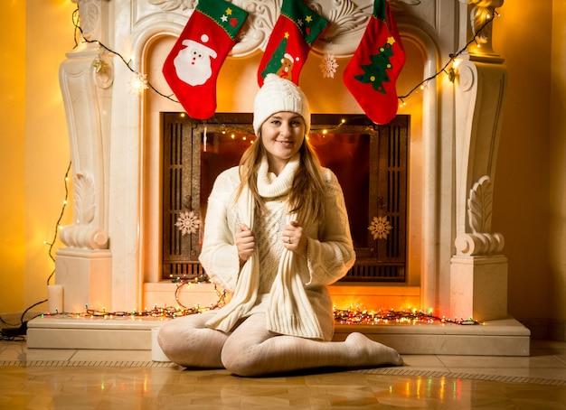 Gelukkige jonge vrouw in witte trui zit bij versierde open haard