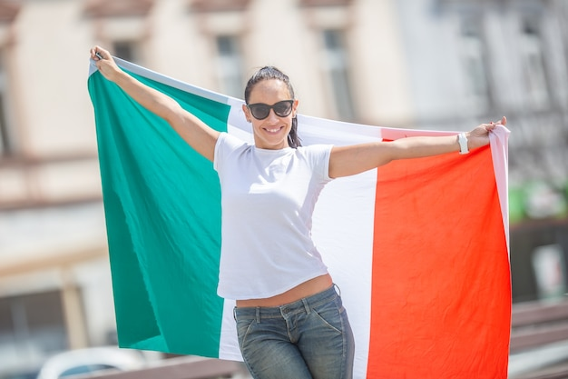 Gelukkige jonge vrouw in zonnebril en wit t-shirt houdt de vlag van italië vast op een straat die feestviert.