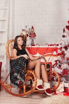 Gelukkige jonge vrouw in zwarte jurk in een schommelstoel en ontspannen in de buurt van de kerstboom