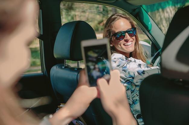 Gelukkige jonge vrouw klaar om auto te rijden op zoek naar haar vriend terwijl ze foto's maakt met een smartphone. vrouwelijke vriendschap en vrije tijd concept.