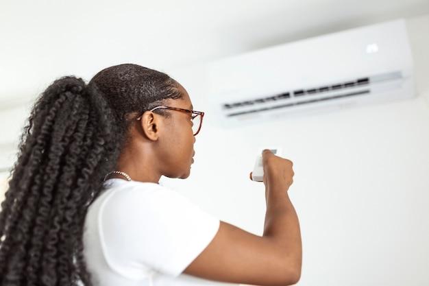 Gelukkige jonge vrouw met afstandsbediening ontspannen onder de airconditioner