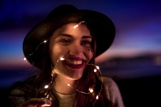 Gelukkige jonge vrouw met brandende slinger op hoofd