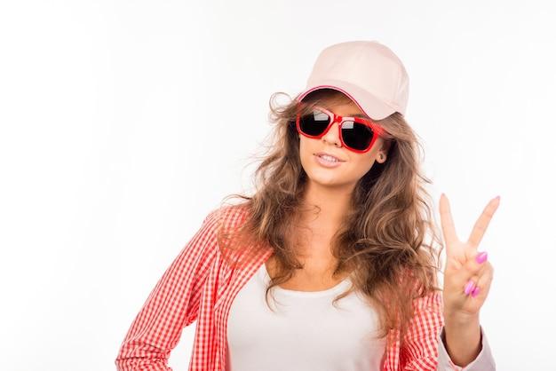Gelukkige jonge vrouw met bril en hoed die twee vingers toont