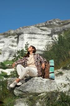 Gelukkige jonge vrouw met bruin haar die pauze hebben tijdens het wandelen met rugzak tussen rotsachtige bergen.