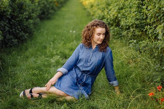 Gelukkige jonge vrouw met bruin krullend haar, dat een kleding draagt, die in openlucht in een tuin stelt