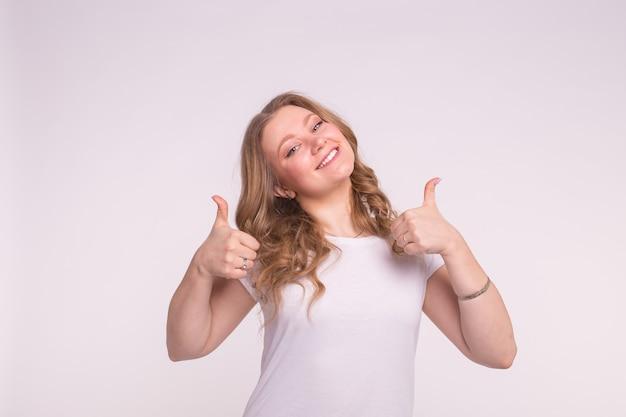 Gelukkige jonge vrouw met duimen omhoog op witte muur.