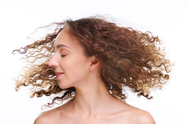 Gelukkige jonge vrouw met een gezonde huid die haar hoofd met donker lang golvend haar dwarrelt tijdens het drogen na het wassen met hydraterende shampoo