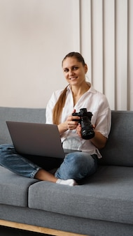 Gelukkige jonge vrouw met fotocamera die laptop thuis met behulp van. de fotograaf houdt de camera vast en lacht. verticale foto.