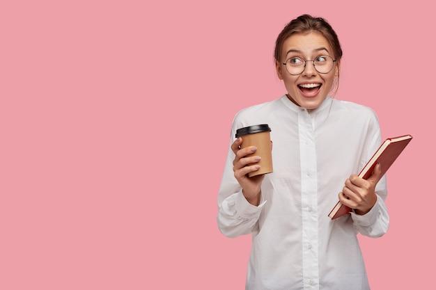 Gelukkige jonge vrouw met glazen die tegen de roze muur stellen