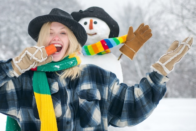 Gelukkige jonge vrouw met grappige wortelneus van sneeuwman.