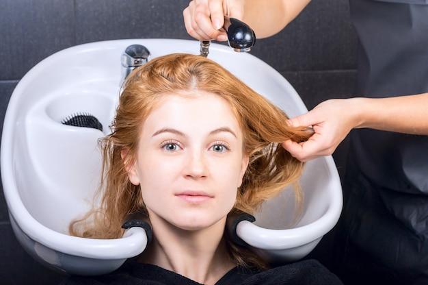 Gelukkige jonge vrouw met het hoofd van de kapperwas bij haarsalon op een donkere muur. schoonheid en mensenconcept