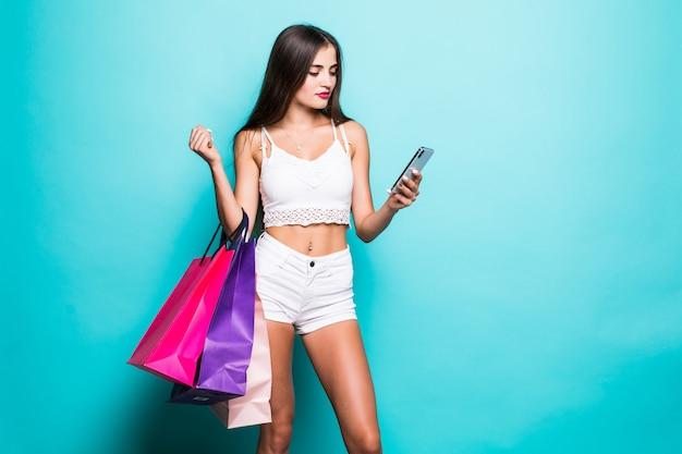 Gelukkige jonge vrouw met het winkelen zakken en telefoon op turkooise muur