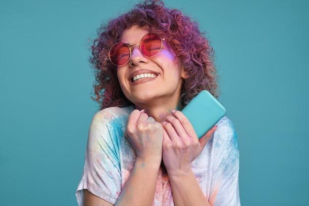 Gelukkige jonge vrouw met holi-kleuren en smartphone