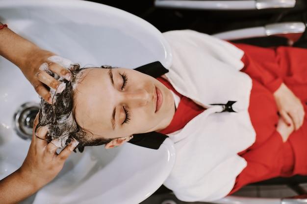 Gelukkige jonge vrouw met hoofd van de kapper het wassen bij kapsalon