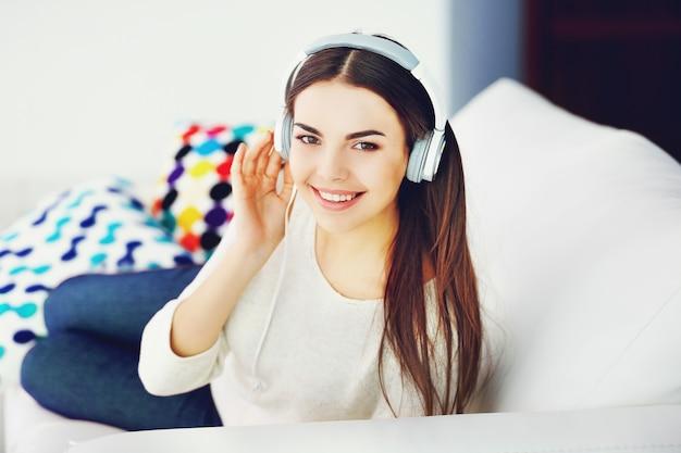 Gelukkige jonge vrouw met koptelefoon luisteren naar muziek op een bank thuis