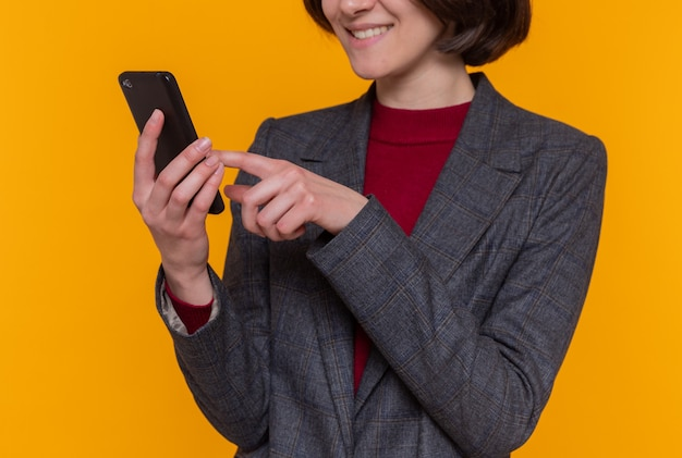 Gelukkige jonge vrouw met kort haar die de grijze smartphone van de jasjeholding dragen