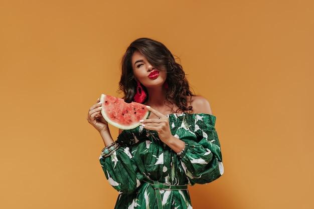 Gelukkige jonge vrouw met krullend donker haar en rode lippenstift in oorbellen en bedrukte groene jurk poseren met watermeloen op oranje muur