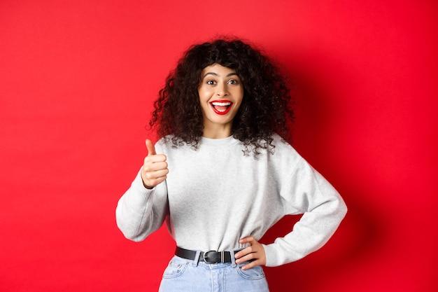 Gelukkige jonge vrouw met krullend haar die goed werk prees, goed gedaan zegt en duim omhoog gebaar toont, keurt en prijst, staande op rode achtergrond.