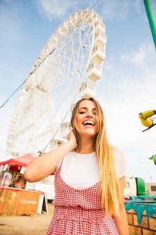 Gelukkige jonge vrouw met lang blonde haar die zich voor ferriswiel bevinden