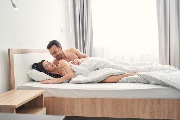 Gelukkige jonge vrouw met lang donker haar die lacht naar haar aantrekkelijke liefhebbende echtgenoot in bed