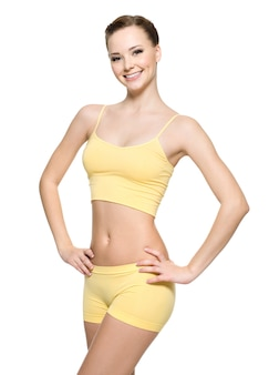 Gelukkige jonge vrouw met mooi slank lichaam in gele sportkleren - die op witte muur wordt geïsoleerd