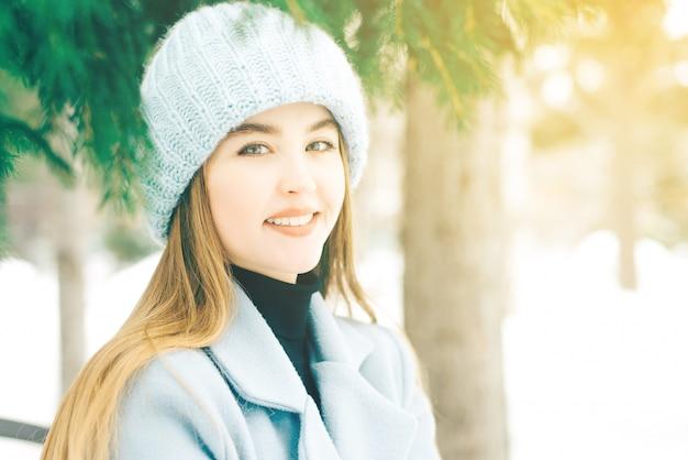 Gelukkige jonge vrouw met mooie blauwe ogen met natuurlijke samenstelling in een zoete glimlach in een gebreide hoed in een blauwe laag op openlucht.