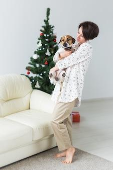 Gelukkige jonge vrouw met mooie hond in woonkamer met kerstboom