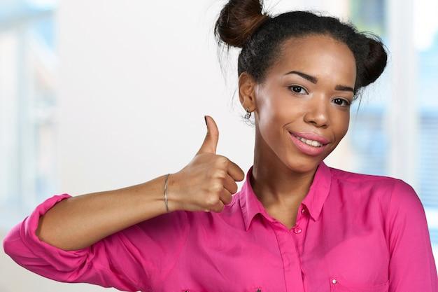Gelukkige jonge vrouw met omhoog duimen