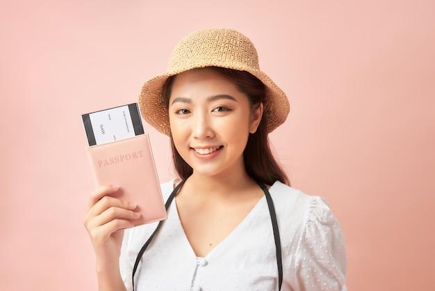 Gelukkige jonge vrouw met paspoort glimlachend en camera kijken tijdens het kopen van kaartjes voor zomervakantie tegen roze