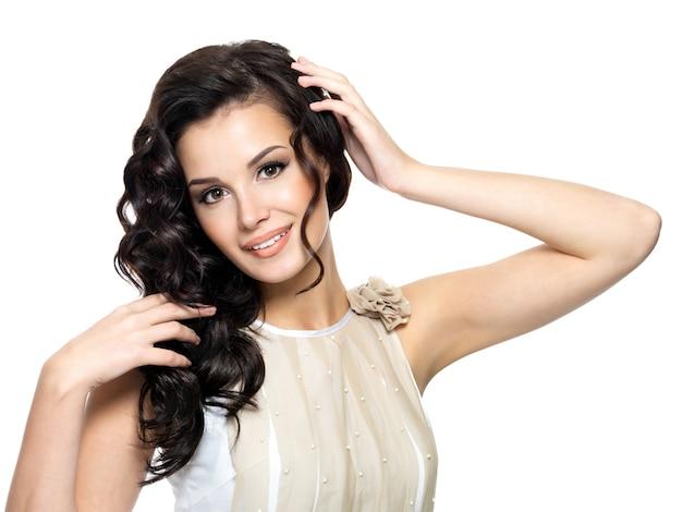 Gelukkige jonge vrouw met schoonheids lang krullend haar - dat op wit wordt geïsoleerd