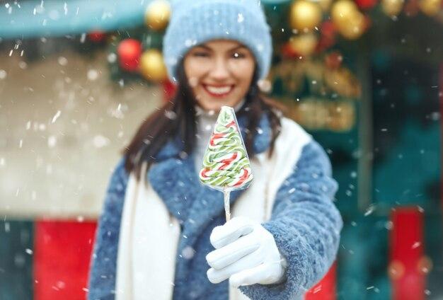 Gelukkige jonge vrouw met snoep op de kerstmarkt tijdens de sneeuwval