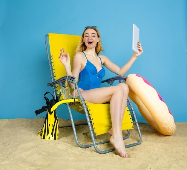 Gelukkige jonge vrouw met tablet neemt selfie of vlog over reizen op blauwe ruimte