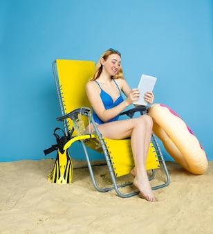 Gelukkige jonge vrouw met tablet neemt selfie of vlog over reizen op blauwe studioachtergrond. concept van menselijke emoties, gezichtsuitdrukking, zomervakantie, weekend. zomer, zee, oceaan, alcohol.