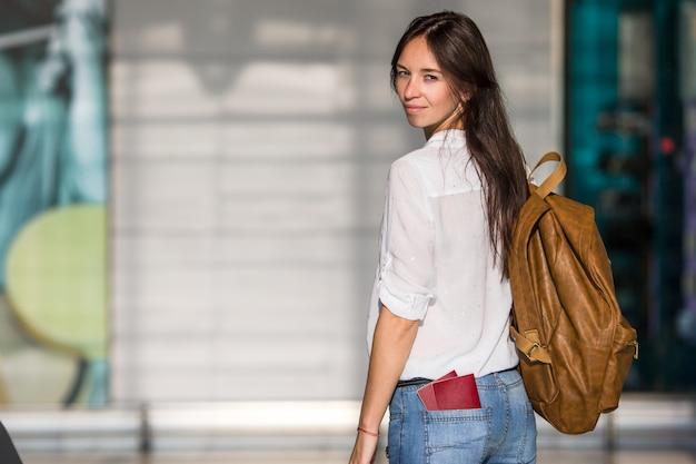 Gelukkige jonge vrouw met vliegticket en paspoorten op luchthaven wachten voor instappen
