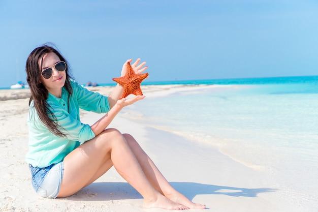 Gelukkige jonge vrouw met zeester op wit strand binnen in het natuurreservaat