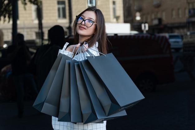 Gelukkige jonge vrouw na het winkelen met zwarte tassen. black friday, verkoop, korting.
