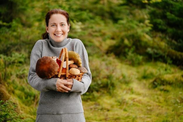 Gelukkige jonge vrouw op de achtergrond van een groen bos houdt een rieten mand met paddenstoelen vast
