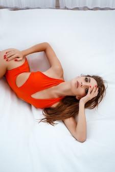 Gelukkige jonge vrouw op het strand. openluchtmanierportret van glamourdame die van haar vakantie op luxevilla in heet tropisch eiland geniet. sexy perfecte pasvorm lichaamsvrouw.