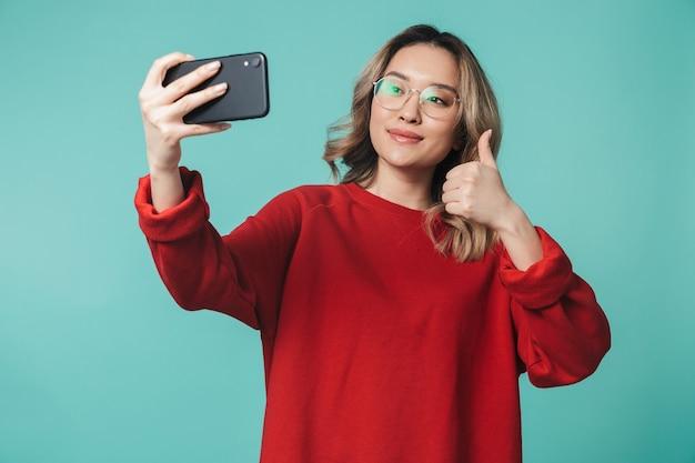 Gelukkige jonge vrouw poseren geïsoleerd over blauwe muur muur praten via mobiele telefoon neem een selfie met duimen omhoog