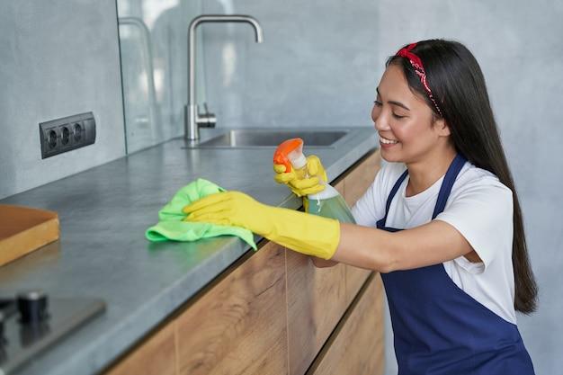 Gelukkige jonge vrouw, schoonmaakster die lacht terwijl ze de keuken schoonmaakt en de oppervlakken besproeit met wasmiddel uit een spuitfles. huishoudelijk werk en huishouden, schoonmaakserviceconcept