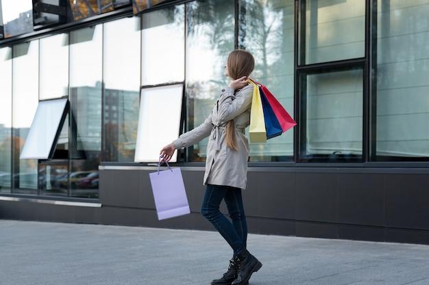 Gelukkige jonge vrouw shopaholic met kleurrijke zakken dichtbij wandelgalerij, die op de straat lopen.