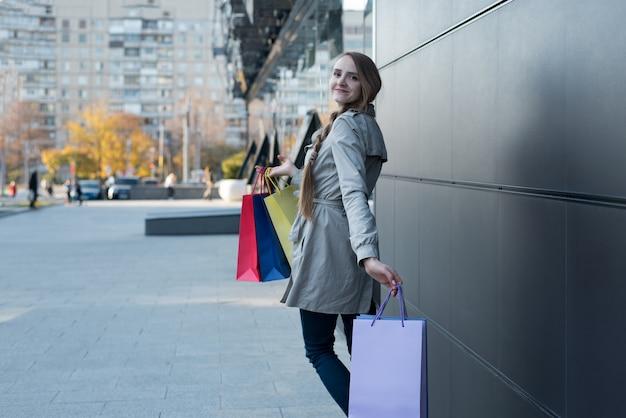 Gelukkige jonge vrouw shopaholic met kleurrijke zakken dichtbij wandelgalerij. lopen op straat.