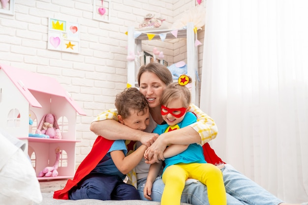 Gelukkige jonge vrouw speelt met haar kinderen als superhelden hen knuffelt