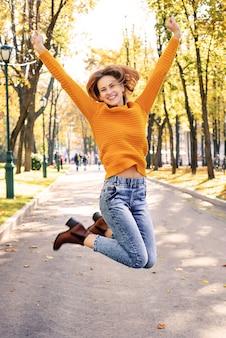 Gelukkige jonge vrouw springen in de herfst in het park