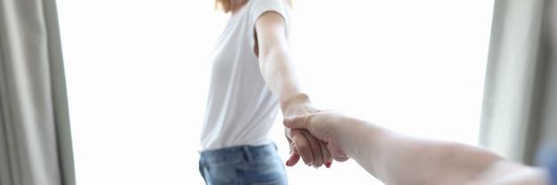 Gelukkige jonge vrouw steekt de hand uit naar de man