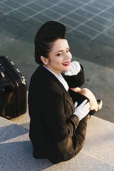 Gelukkige jonge vrouw stewardess in uniform glimlachend en wachtend op haar vliegtuig