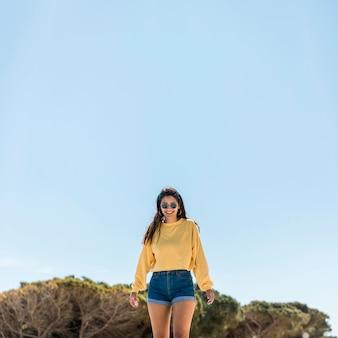 Gelukkige jonge vrouw tegen blauwe hemel in aard