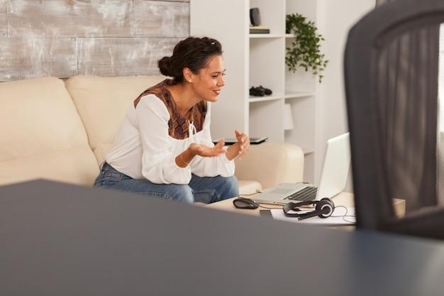 Gelukkige jonge vrouw tijdens een videogesprek terwijl ze vanuit huis werkt.
