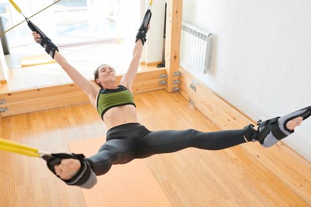 Gelukkige jonge vrouw vastgebonden aan yoga swing